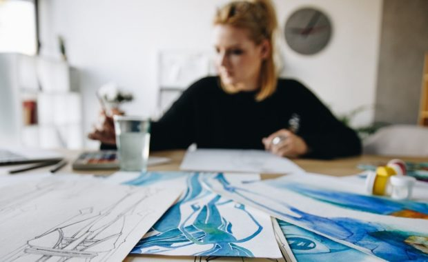 woman with drawings at desk
